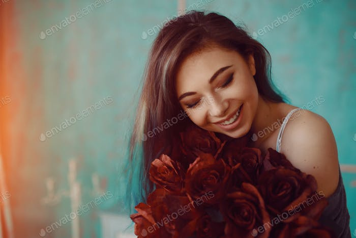 Young and beautiful woman with bouquet of roses
