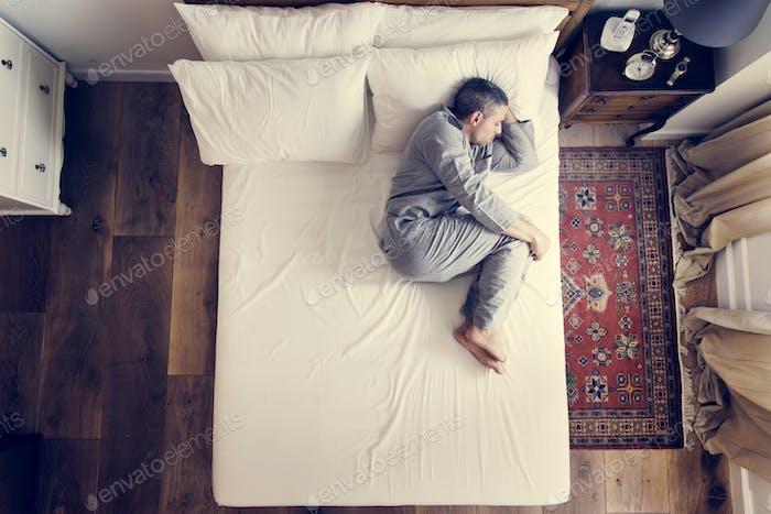 Französisch Mann schlafen allein auf dem Bett