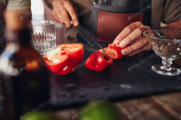 Bartender hands chopping red bell pepper