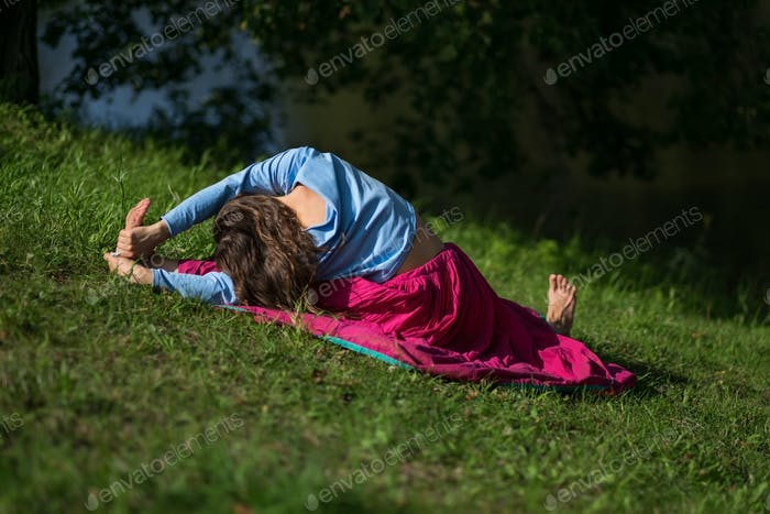 Woman practices yoga asana in park in the morning.