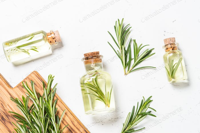 Rosemary essential oil in the bottle on white