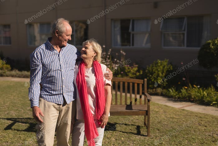 Front view of active senior Caucasian couple standing with arm around in the park