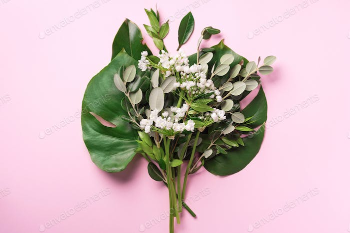 Spring flowers and tropical monstera leaves. Floral composition, creative layout. Flat lay, top view