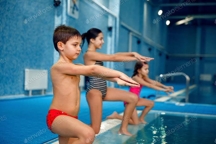 Children swimming group, workout at the poolside