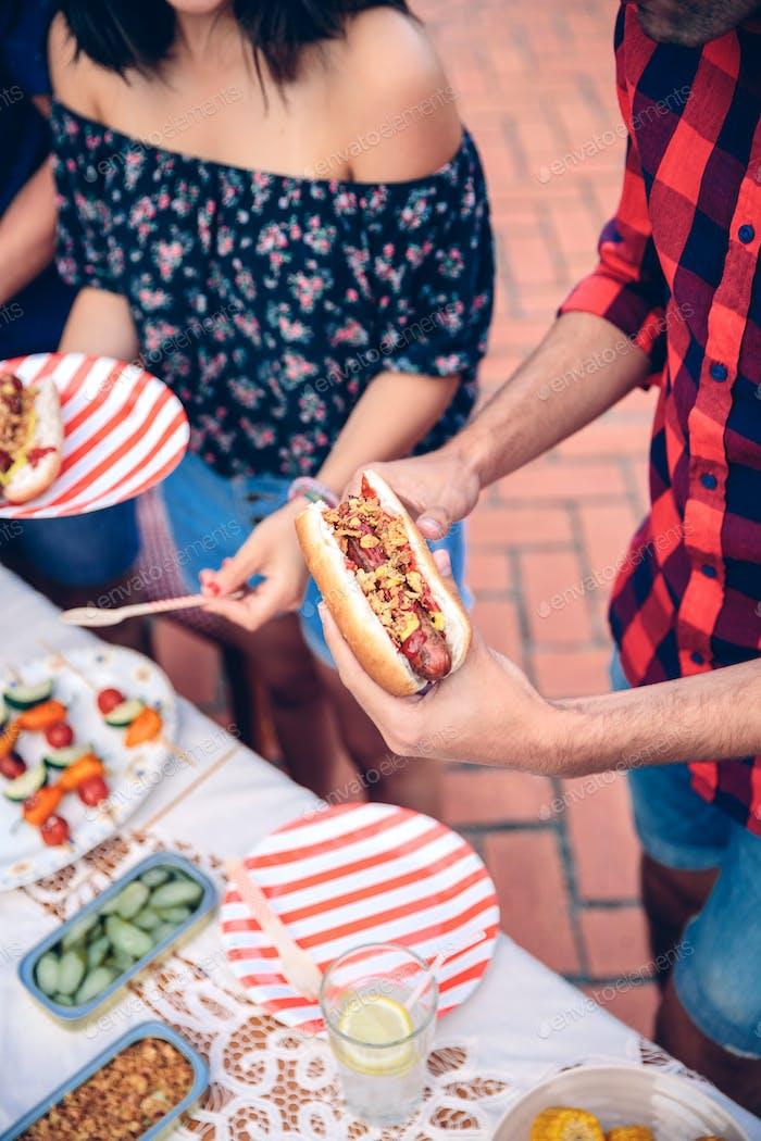Mann hält Hotdog im Barbecue mit Freunden