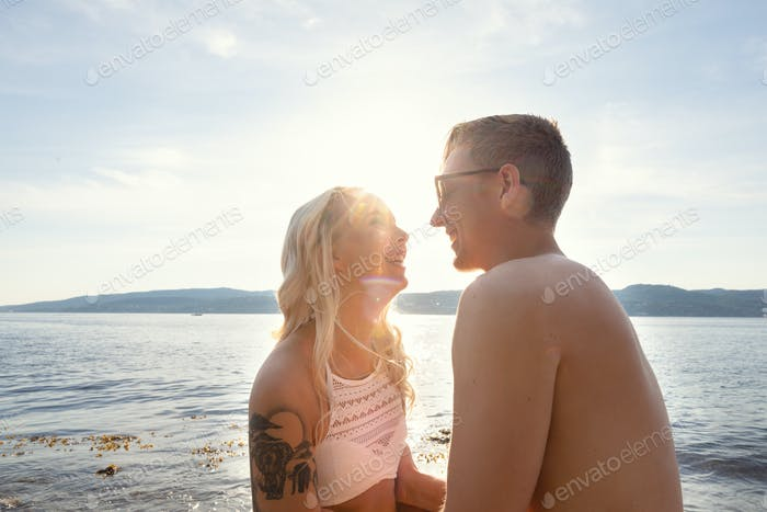 Laughing couple in love laughing at the beach against sun