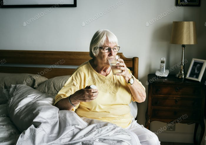 Senior woman having pills on her bed