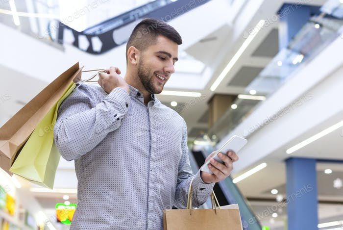 Happy guy with cellphone and purchases in shopping center