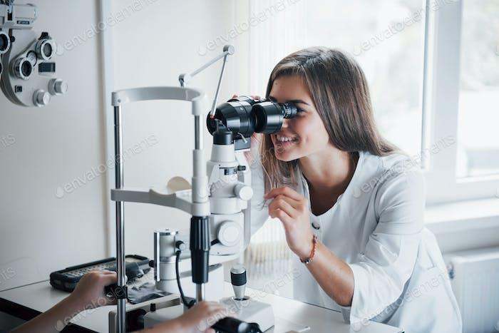 Junge Ärztin arbeitet mit dem Augentestgerät und lächelt