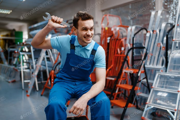 Smiling male worker holds wrench in tool store