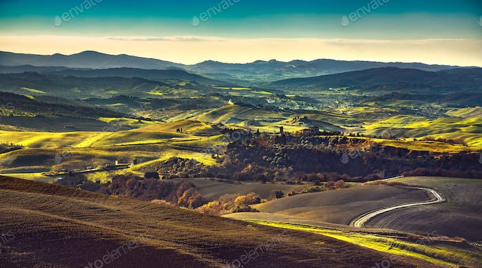 Volterra winter panorama, rolling hills and green fields on suns