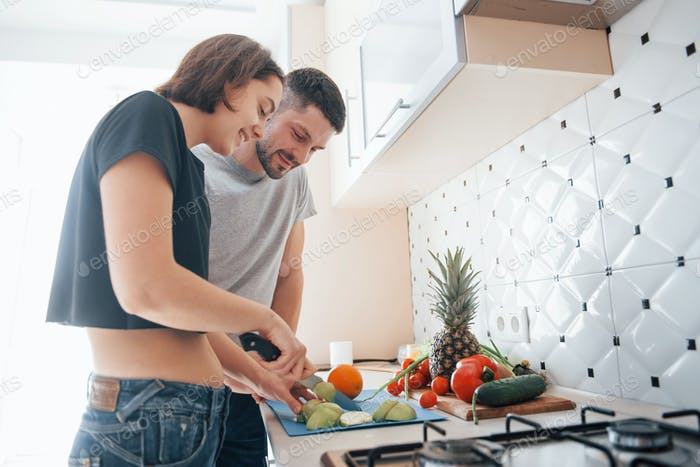 Young couple in the modern kitchen at home at their weekend time in the morning