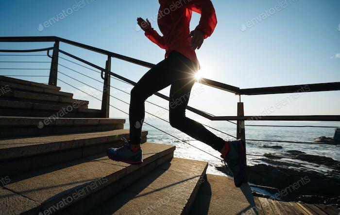 Runner legs running upstairs on sunrise seaside