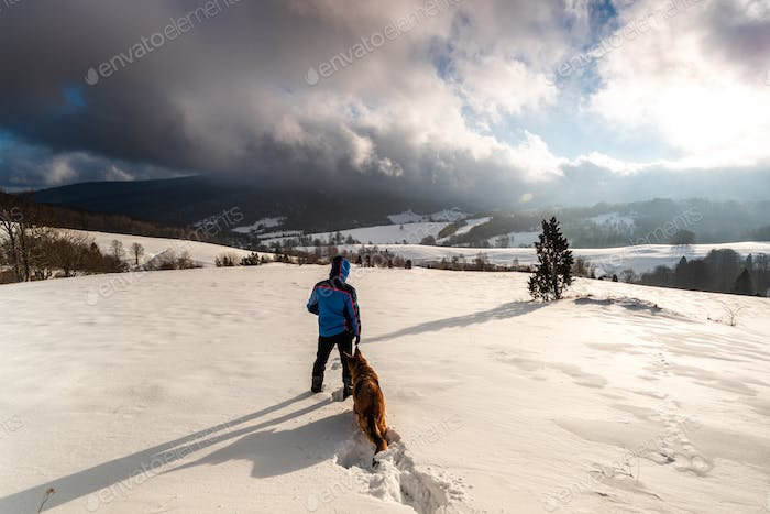 Active Couple Man and Dog Walking in Deep Snow. Outdoor Adventure