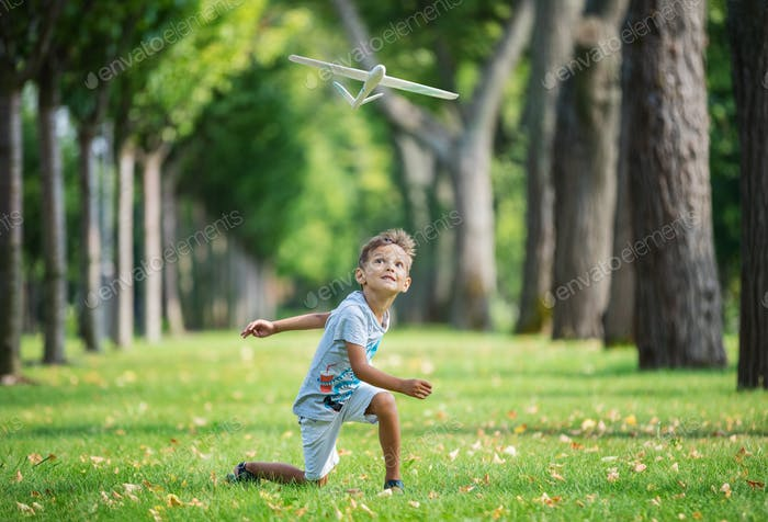 Thumbnail for Boy playing with toy glider in park on summer day