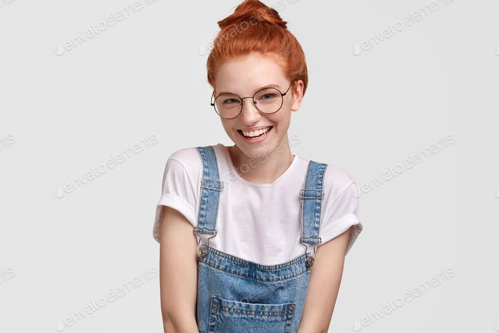 Positive glad red haired female has positive smile, dressed in denim dungaree, smiles happily at cam