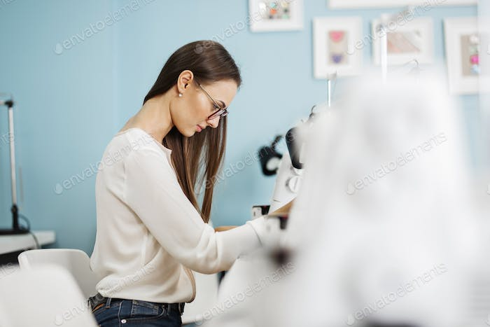 A smart-looking pretty brunet woman wearing white shirt is sewing with the electric sewing-machine