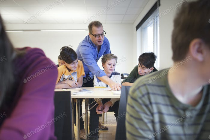 Teacher explaining schoolchildren (12-13) task in classroom