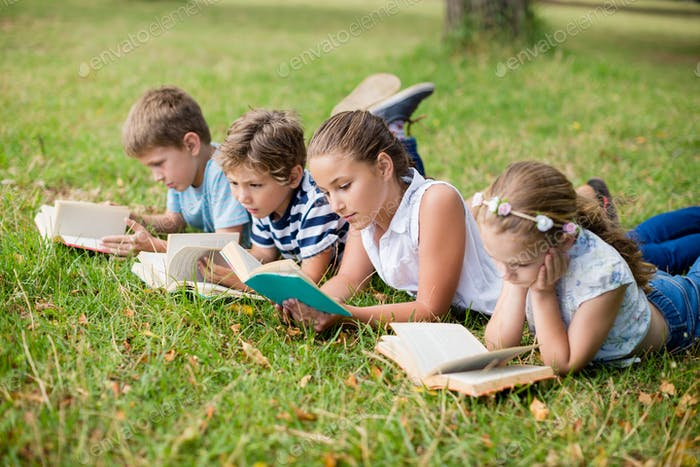 Kids lying on grass and reading books
