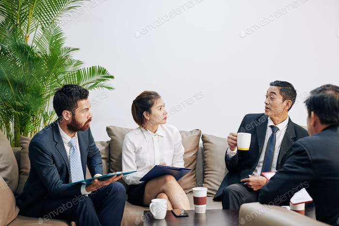 Businessman sharing thoughts with coworkers