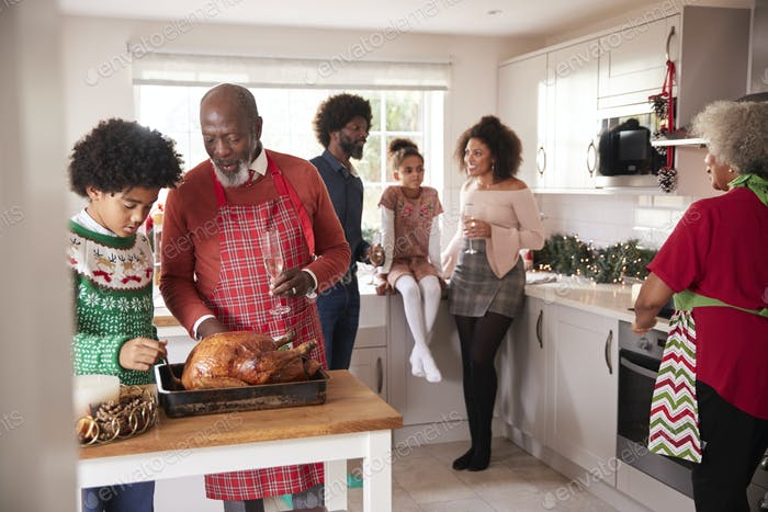 Mixed race, multi generation family gathered in kitchen before Christmas dinner