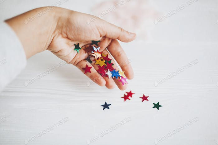 Hand holding colorful sparkling stars decorations on white background