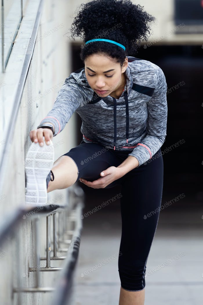 Fit and sporty young woman doing stretching in city.