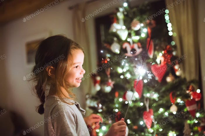 Little girl with a sparkler in front of Christmas tree.