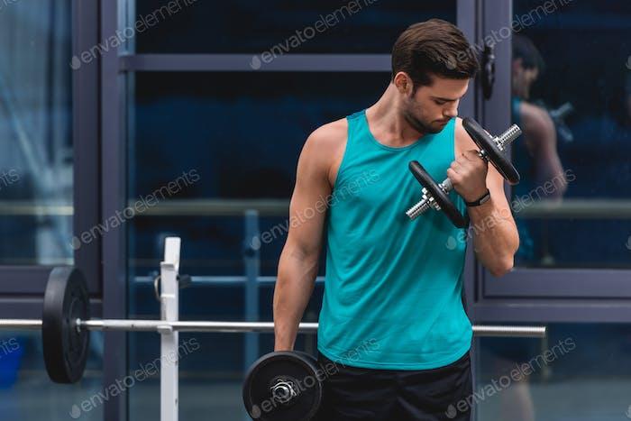 тренировка мускулистого спортсмена с гантелями в тренажерном зале
