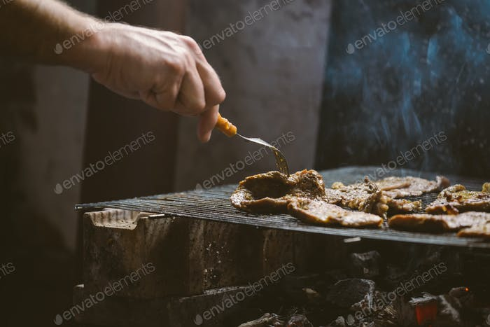 Man grilling pork meat chops on barbecue