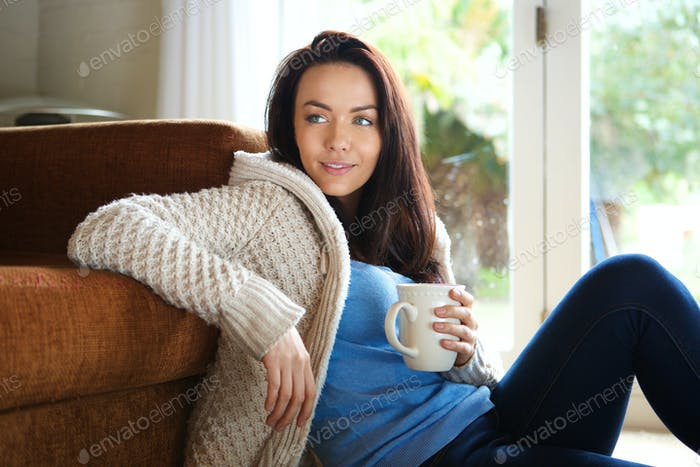 Young woman sitting floor with cup of tea