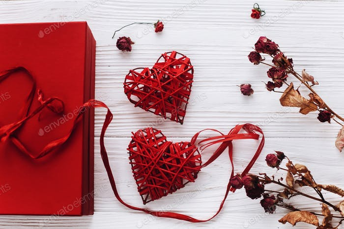 luxury red present with ribbon and hearts on white rustic wooden background