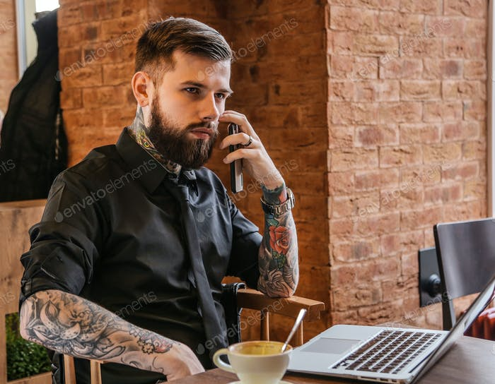 Man with tattoo calling by smartphone.