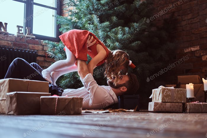 Dad and daughter have fun together while lying on the floor, surrounded by gifts