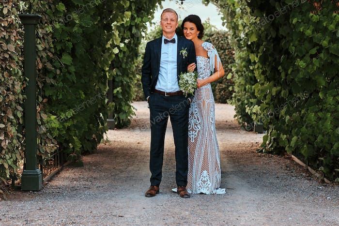 Happy wedding couple is walking by a beautiful garden.