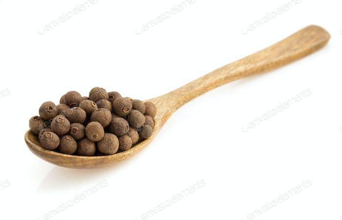 allspice in spoon  on white