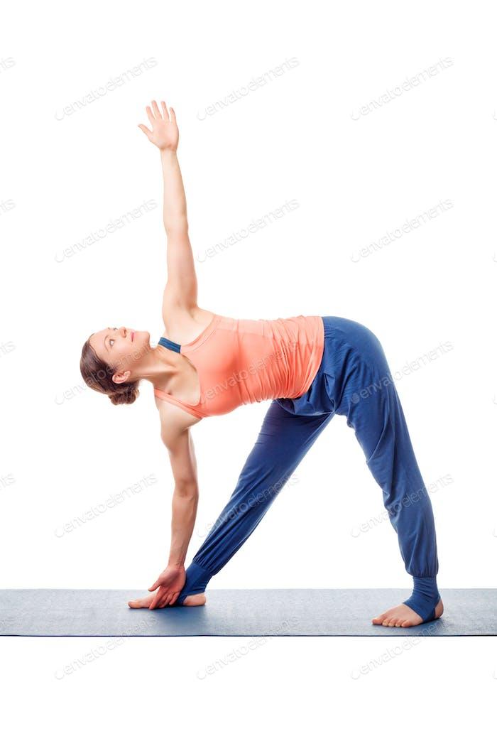 Sporty fit woman practices yoga asana utthita trikonasana