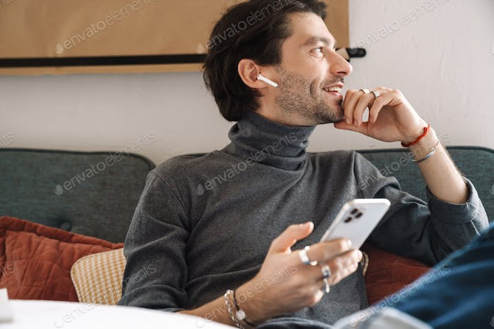 Image of caucasian young man wearing earbuds using smartphone in cafe