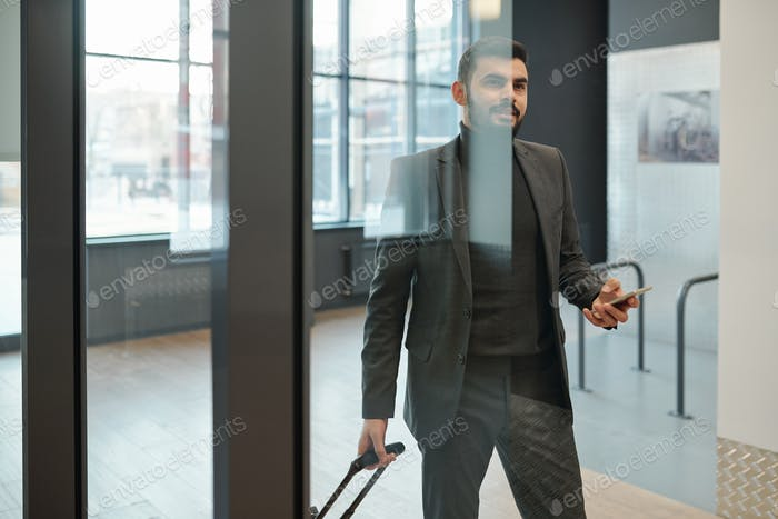 Contemporary young businessman in formalwear with suitcase standing by door
