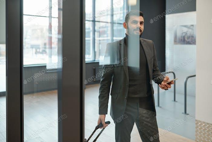 Zeitgenössischer junger Geschäftsmann in Formalwear mit Koffer stehen an Tür