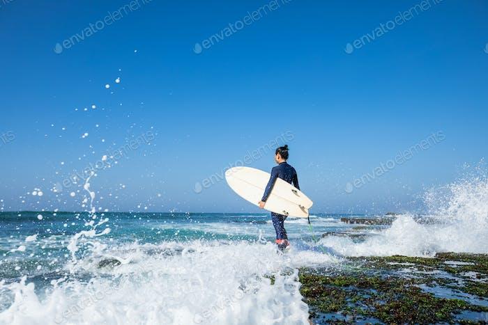 Surfista con tabla de surf en el mar