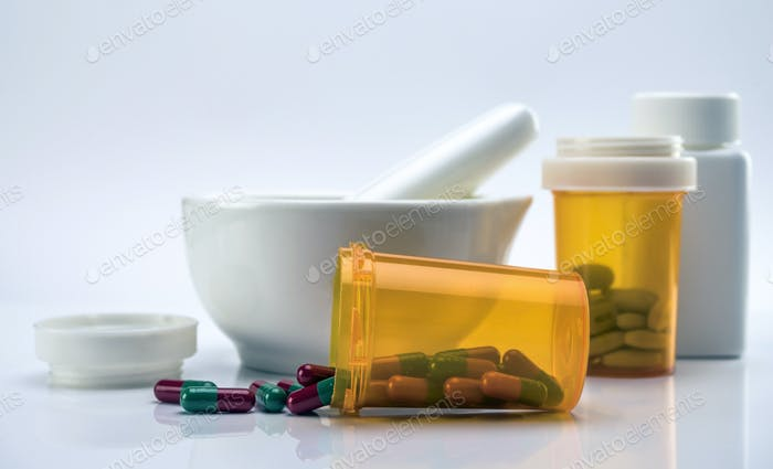 Mortar pharmaceutical next to several cans of capsules isolated on white background