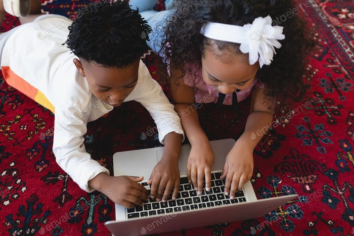 Cute African American sibling lying on floor and using laptop in a comfortable home