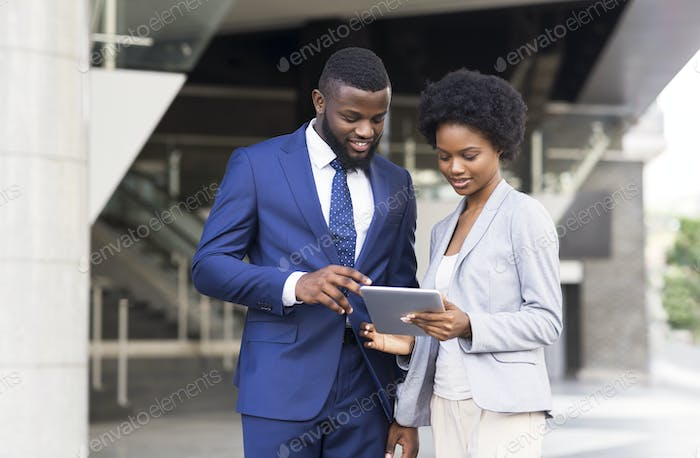 Business people using digital tablet together outdoors