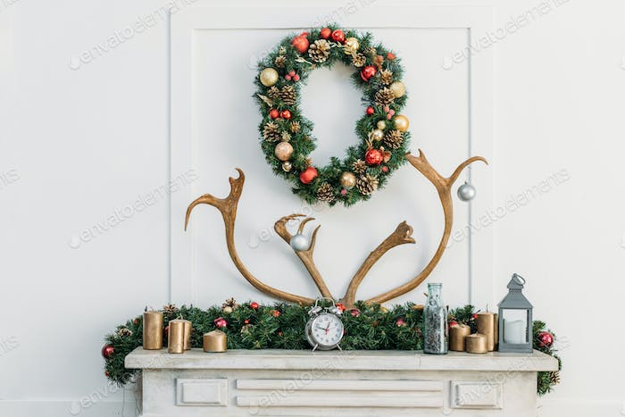 beautiful fireplace decorated with antlers and christmas wreath