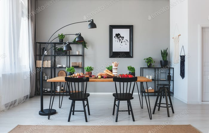 Black chairs and lamp at wooden table with food in grey dining r