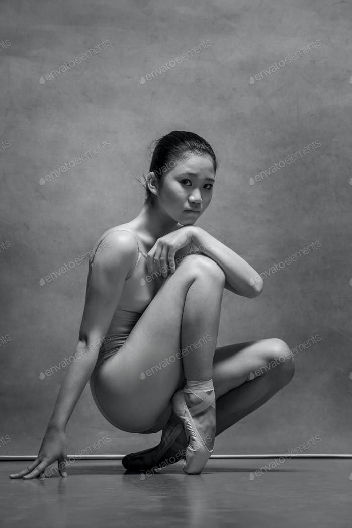 Tired ballet dancer sitting on the wooden chair on a gray background