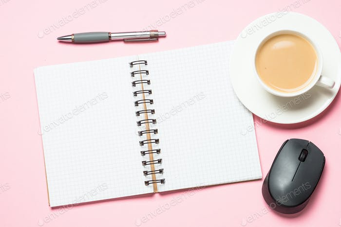 Office workplace with notepad, coffee cup and mouse on pink desk