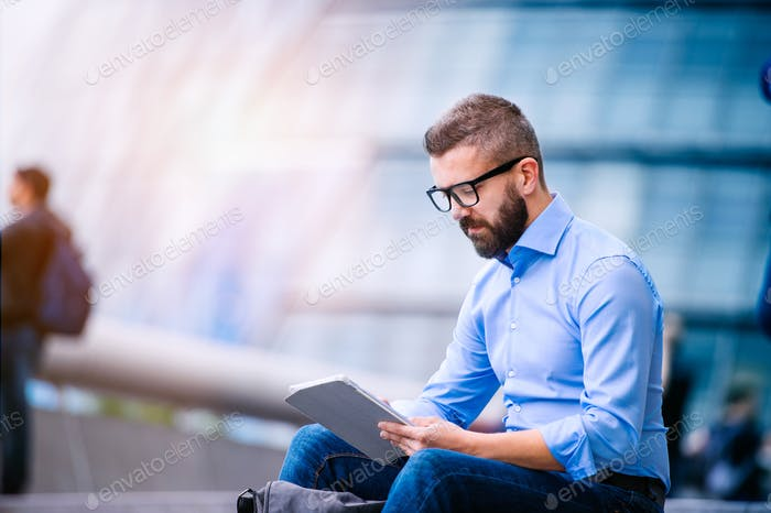 Manager with tablet, sitting on stairs, London, City Hall