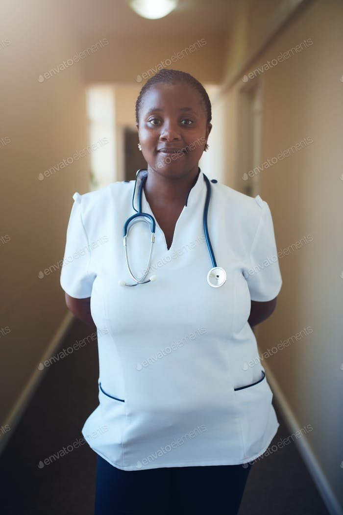 Female healthcare worker standing in hallway